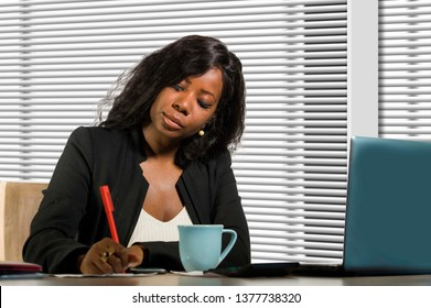 corporate business portrait of young beautiful and busy black African American businesswoman writing notes on desk working with laptop computer at company office in woman job success