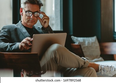Corporate business professional sitting in office lobby working on laptop. Mature male executive working in office lounge.