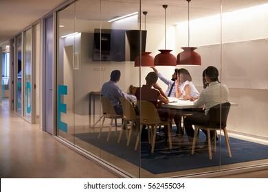 Corporate business team using AV display in meeting cubicle