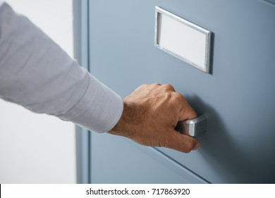 Corporate businessman opening a filing cabinet drawer