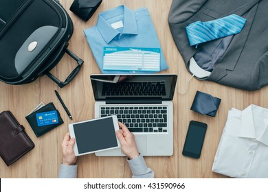 Corporate businessman packing his bag and planning a business trip, he is booking flights online using a digital tablet, travel and technology concept