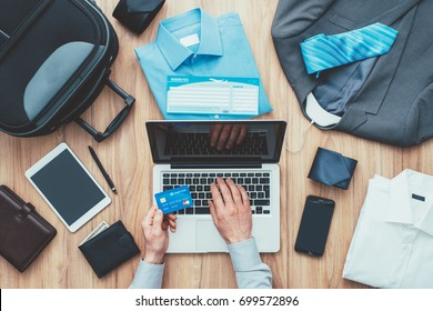 Corporate businessman packing his bag and planning a business trip, he is booking flights online using a laptop and a credit card, travel and technology concept