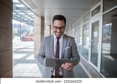 Corporate businessman using tablet for checking e-mail while standing in front of shop window. Waist up portrait.