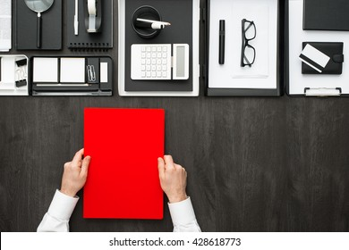 Corporate businessman working at office desk, he is holding a folder, business and finance concept, flat lay