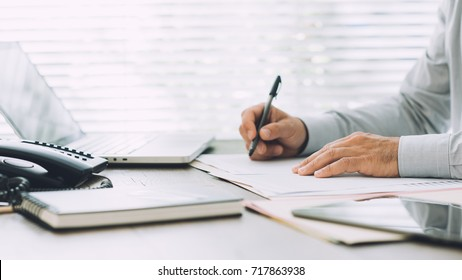 Corporate businessman working at office desk, he is writing paperwork and using a laptop