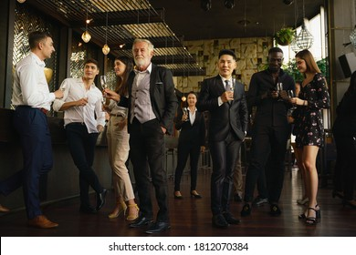 corporate businesspeople having fun and talking together in corporate party in club to celebrate spacial event such as corporate aniversary