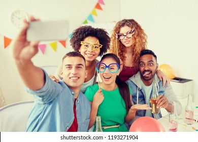 corporate, celebration and holidays concept - happy friends or team with party accessories and non alcoholic drinks taking selfie at office