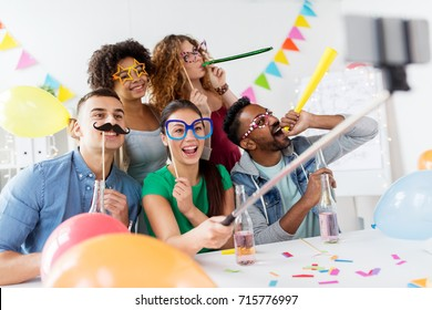 corporate, celebration and holidays concept - happy friends or team with party accessories taking selfie at office