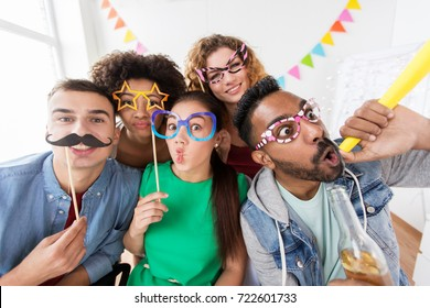 corporate, celebration and holidays concept - happy friends or team with party accessories having fun at office