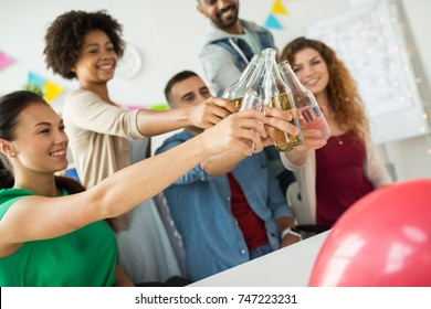 corporate, celebration and holidays concept - happy coworkers clinking bottles with non-alcoholic drinks at office party