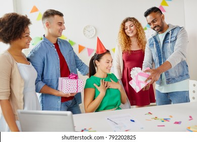 corporate, celebration and people concept - happy team with gifts greeting female colleague at office birthday party