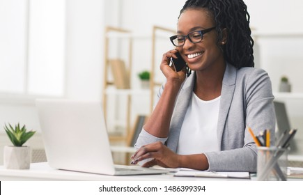 Corporate Communication. Black Businesswoman Talking On Mobile Phone Working On Laptop In Modern Office. Free Space