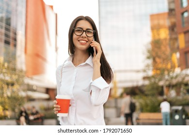 Corporate Communication. Caucasian Businesswoman in eyewear Talking On Mobile Phone with coffee to go on business center background