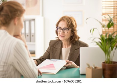 Corporate counselor explaining a graph to her employee during a meeting