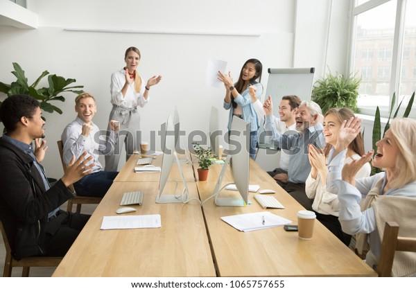 Des collègues d'équipe d'entreprises diverses félicitent les collègues africains motivés par le succès commercial ou la réussite en applaudissant les mains dans le bureau de co-travail, les employés multiraciaux applaudissent excités par les bonnes nouvelles