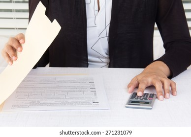 Corporate employee dressed in black suit at workplace is opening a folder and calculating financial data using a calculator.  Office desk is infront of a window with white blinds.