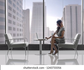 Corporate executive busy on the go in modern high rise, with laptop and coffee
