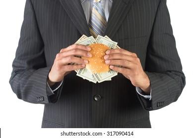 Corporate executive holding a burger stuffed with dollar bills