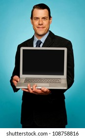 Corporate executive showing blank screen laptop to you. All on gradient background
