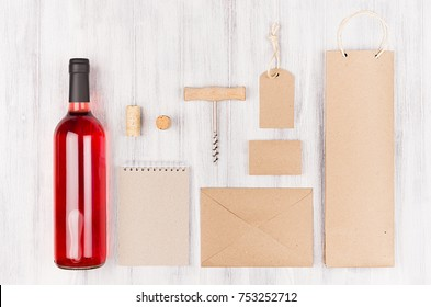 Corporate identity template for wine industry blank beige craft packaging, stationery, merchandise set with bottle rose wine on soft white wood background.