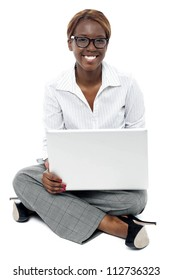 Corporate lady seated on floor working on laptop. Looking at camera and smiling