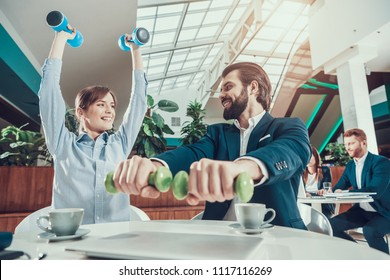 Corporate Lifestyle Healthcare Concept of Business People in Office Interior Working with Dumbbells. Workers Doing Fitness Exercises of Yoga Practice. Wellbeing Employee Man Smiling to Healthy Woman