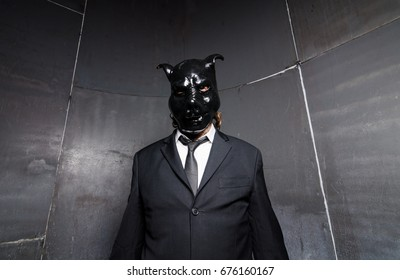 A corporate man in a dirty scruffy suit wearing a black pigs mask in a dark sinister background, photographed with moody cinematic lighting. evil dirty corporate pigs.