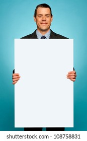 Corporate man holding big white blank billboard isolated over gradient background