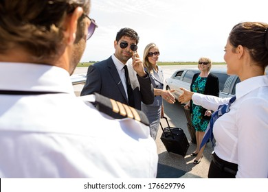 Corporate man and women greeting pilot and airhostess at airport terminal