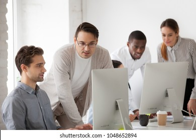 Corporate mentor teaching intern helping and supervising online computer work, team leader or company executive explaining new web design project or programming task to employee at workplace