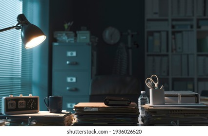 Corporate office interior with piles of paperwork and lit lamp, professional workspace concept