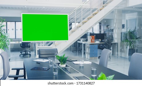 In the Corporate Office Meeting Room Stands Green Mock-up Screen TV or Interactive Digital Whiteboard in Horizontal Mode. In the Background Big Bright Busy Office