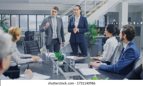 In Corporate Office Meeting Room: Two Young Company Re-Branding Strategists and Trend Growth Development Specialists Deliver Inspiring Speech to a Board of Directors Sitting at the Conference Table