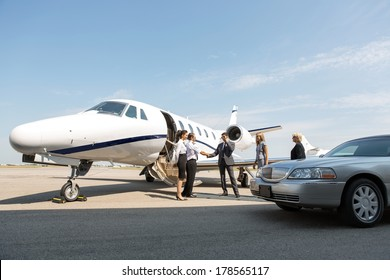 Corporate people greeting airhostess and pilot near private jet and limo at airport terminal
