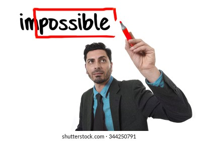 corporate portrait businessman turning impossible word into possible with red marker writing on glass isolated on white background in work motivation,  incentive and challenge concept