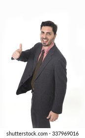 corporate portrait of young attractive businessman of Latin Hispanic ethnicity smiling in suit and tie standing isolated on white background giving thumb up in business success concept