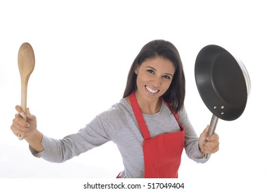 corporate portrait of young attractive hispanic home cook woman in red apron posing happy and smiling holding spoon and pan isolated on white background in chef and successful cooking