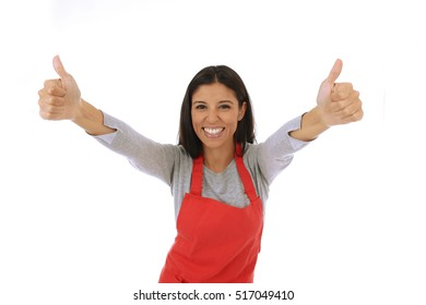 corporate portrait of young attractive hispanic home cook woman in red apron posing happy and smiling giving thumb up isolated on white background in chef and successful cooking