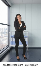 corporate portrait of young attractive latin woman wearing formal suit smiling happy and confident at modern office next to window in business success concept