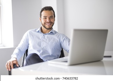 A corporate portrait young mexican attractive businessman on his 30s working at modern home office with computer laptop