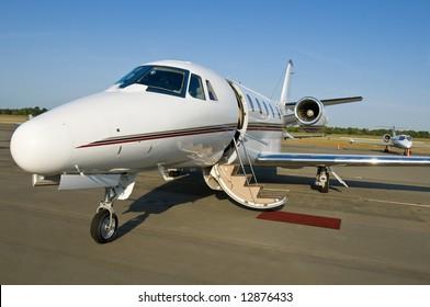 Corporate private luxury jet at airport door open blue sky