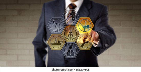 Corporate service manager in blue suit activating an oil rig icon on an interactive remote control screen. Oil and gas industrial technology and services concept for exploration and production.