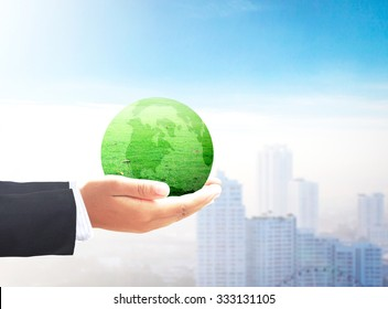 Corporate social responsibility (CSR) concept: Businessman hand holding earth globe of grass over blurred city background