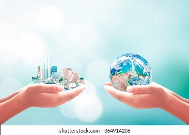 Corporate social responsibility (CSR) concept: Two human hand holding big city and earth globe over blurred blue nature background. Elements of this image furnished by NASA