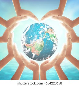 Corporate social responsibility (CSR) concept: Heart shape of hands holding earth globe over blurred blue sky background. Elements of this image furnished by NASA