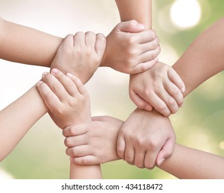 Corporate social responsibility CSR on children's friendship education, teamwork empowerment and go green concept with kids and friends holding hands together isolated on natural background