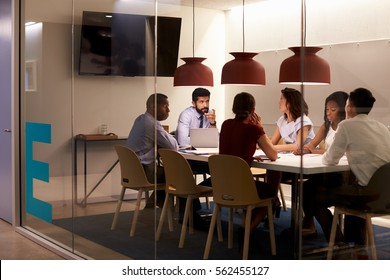 Corporate team at table in a meeting room cubicle, close up