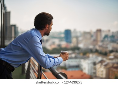 Corporate time-out. Waist up portrait of young businessman standing on office balcony while having coffee break and looking at city view. Copy space on right
