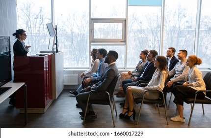 Corporate training concept. Business coach giving presentation to young staff at conference room, side view