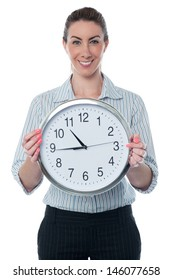 Corporate woman displaying wall clock